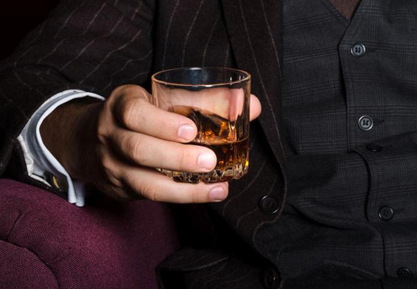 A man with a whiskey glass